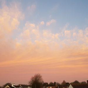 Anxious about coronavirus? Image of relaxing sunset view over houses and trees, with peaches and blues and fluffy clouds